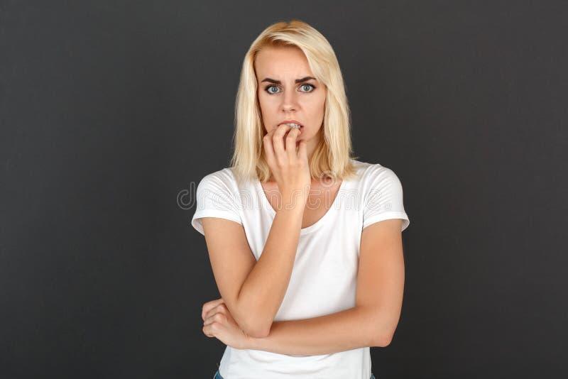 freestyle Situación de la mujer aislada en los clavos que muerden de la pared negra nerviosos fotografía de archivo