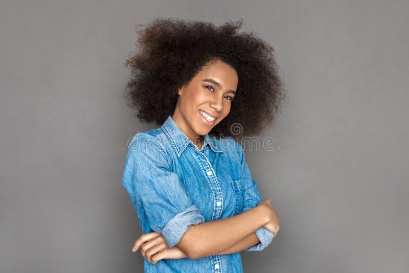 freestyle Situación de la mujer del mulato aislada en los brazos cruzados grises que ríen el primer tímido foto de archivo libre de regalías