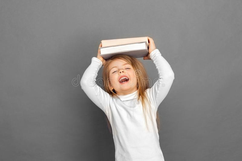 freestyle Situación de la niña aislada en gris con los libros sobre la risa de la cabeza alegre fotografía de archivo