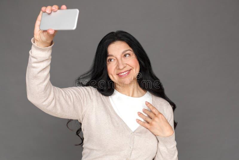 freestyle Situación madura de la señora aislada en selfie que toma gris en la sonrisa del smartphone alegre foto de archivo libre de regalías