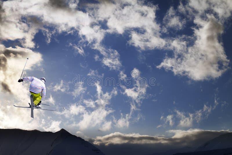 Freestyle ski jumper met doorgestreept ski's in bergen bij zonsondergang stock afbeeldingen