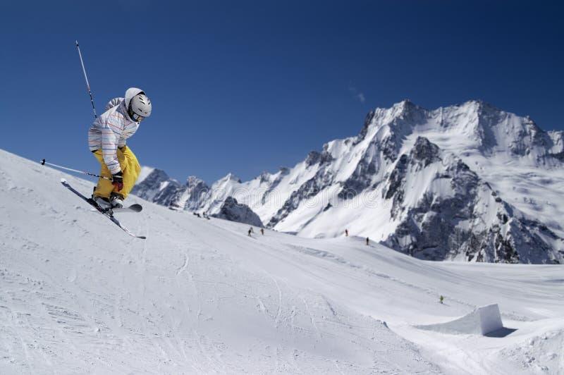 Freestyle ski jumper met doorgestreept ski's tegen sneeuwbergen stock fotografie