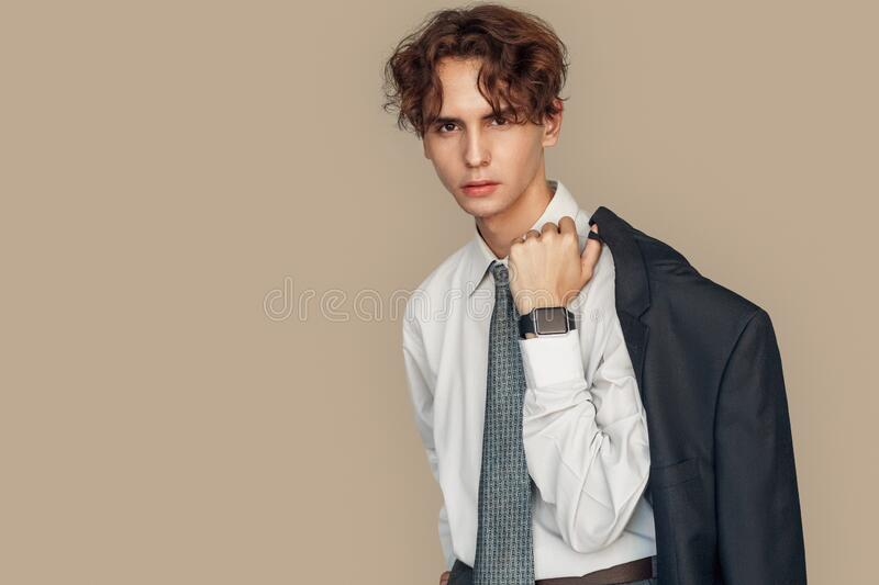 Freestyle. Young businessman with digital watch standing  on gray holding blazer confident. Young stylish businessman wearing digital watch standing  on gray stock photography