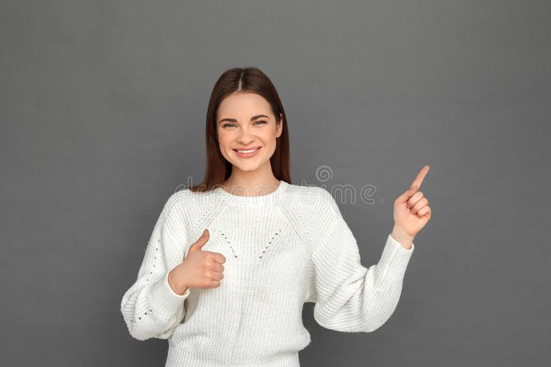 Freestyle. Young girl standing on grey pointing at space aside thumb up smiling happy royalty free stock image