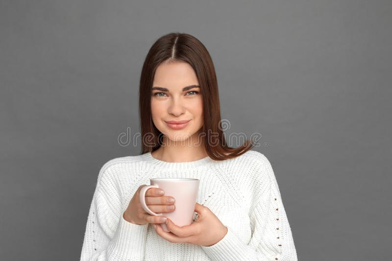 Freestyle. Young girl standing isolated on grey drinking hot coffee smiling happy close-up stock photos