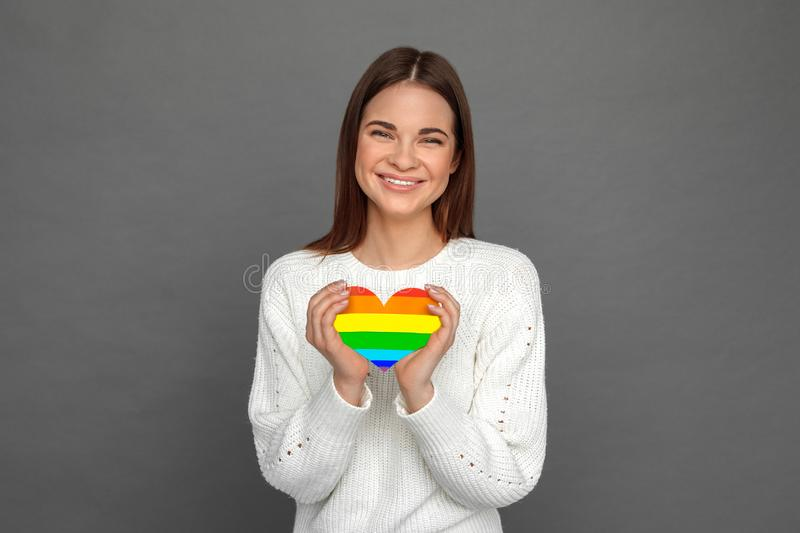 Freestyle. Young girl standing isolated on grey with lgbt colored heart card smiling cheerful stock photography