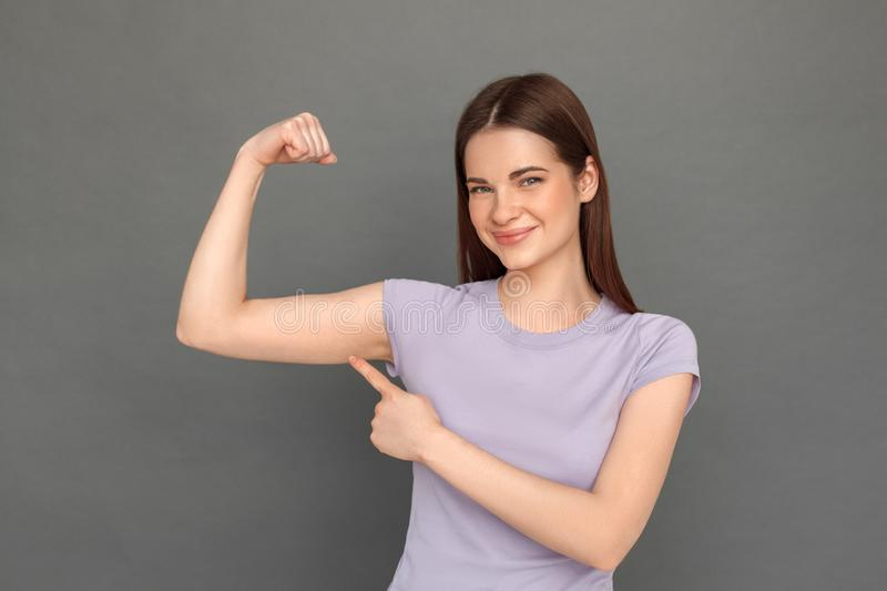 Freestyle. Young girl standing isolated on grey showing arm muscle smiling confident close-up stock photo