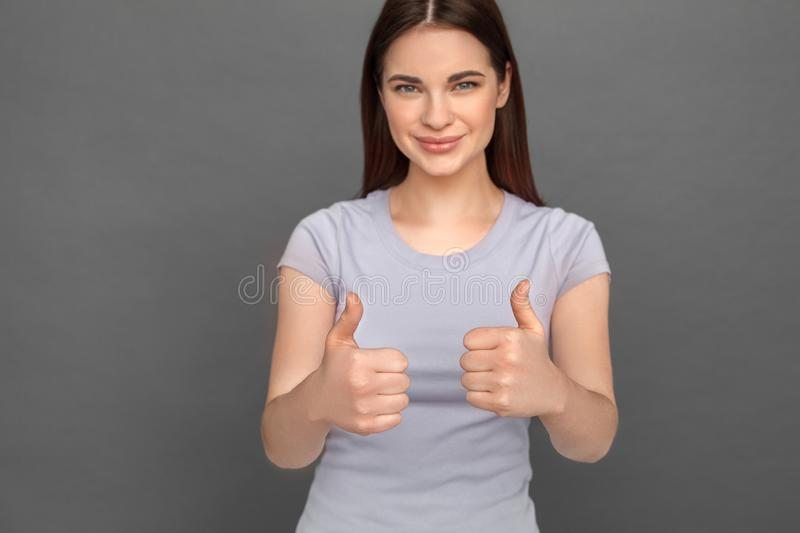 Freestyle. Young girl standing isolated on grey showing thumbs up smiling happy close-up stock image