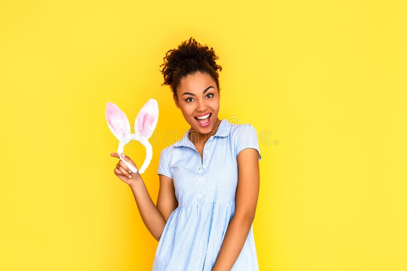 Freestyle. Young woman in cute dress standing isolated on yellow with bunny ears smiling cheerful to camera stock image