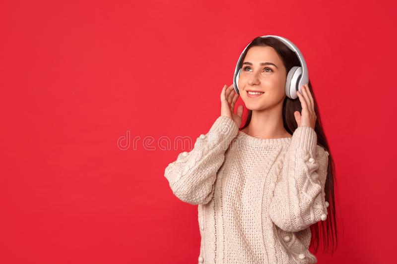 Freestyle. Young woman in headphones standing isolated on red listening music looking up smiling happy royalty free stock images