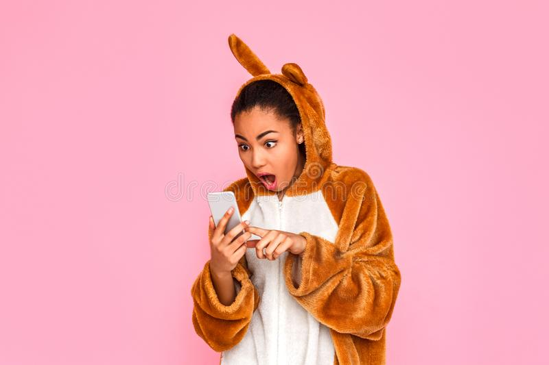 Freestyle. Young woman in kigurumi standing isolated on pink looking at screen of smartphone shocked royalty free stock photo
