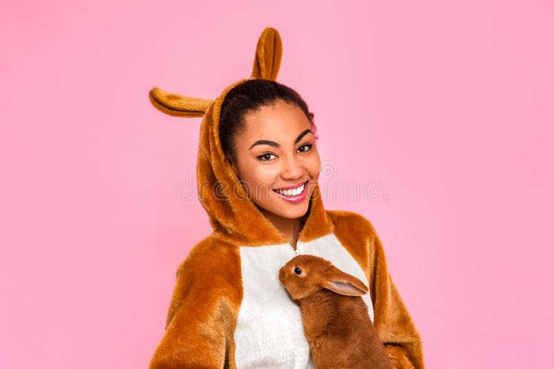 Freestyle. Young woman in kigurumi standing isolated on pink with rabbit smiling confident close-up stock photography