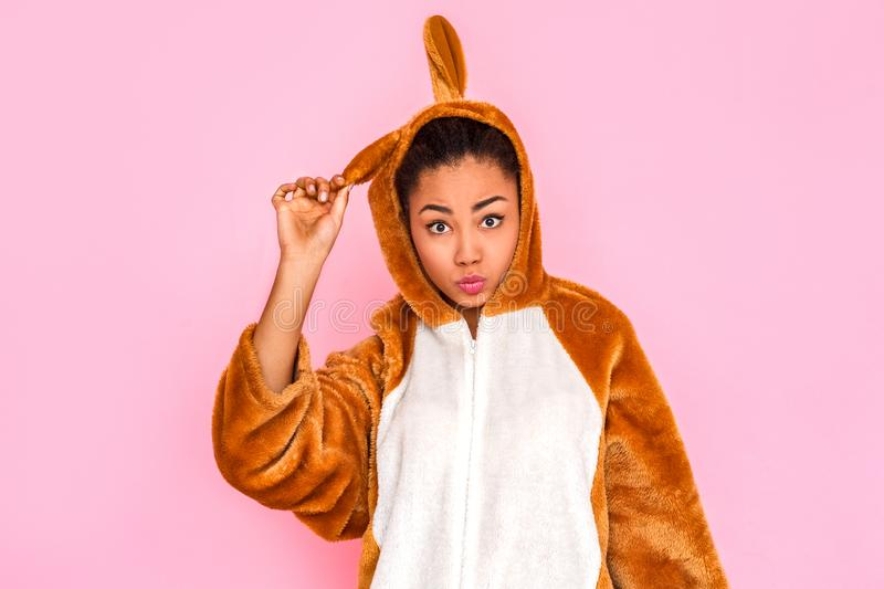 Freestyle. Young woman in kigurumi standing isolated on pink touching rabbit ear grimacing to camera royalty free stock photos