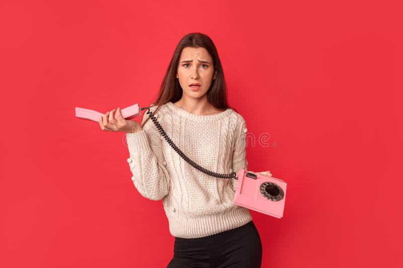 Freestyle. Young woman standing isolated on red with stationary phone handset looking camera concerned royalty free stock photos