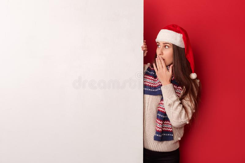 Freestyle. Young woman wearing scarf and santa hat standing isolated on red looking at white board surprised stock image