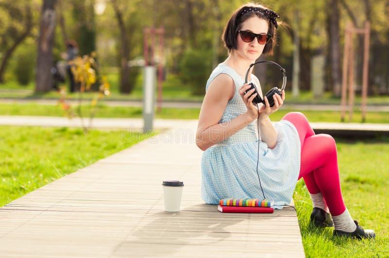 Freetime begrepp med kvinnlig avslappnande det fria med musik och Co royaltyfria bilder