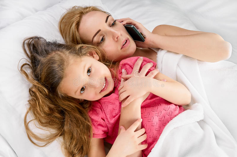 Freetime da filha da mãe na cama imagens de stock