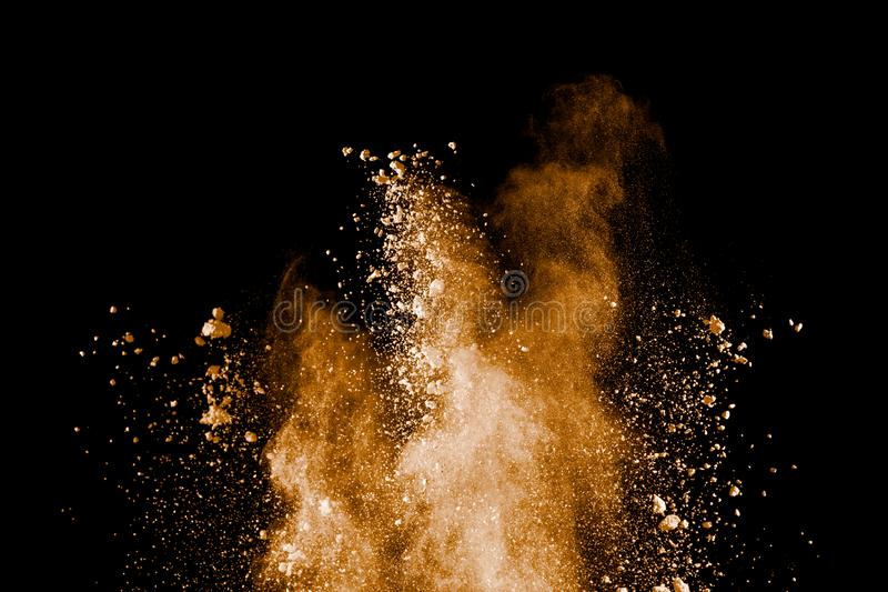 Freeze motion of brown dust explosion.Stopping the movement of brown powder. Explosive brown powder on black background stock images