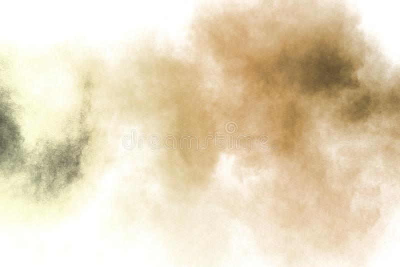 Freeze motion of brown dust explosion on white background. Throwing brown powder out of hand against white background royalty free stock images