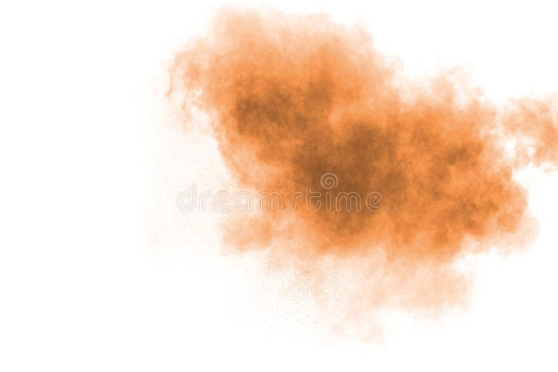 Freeze motion of brown powder exploding. Abstract design of color powder cloud against white background stock photography