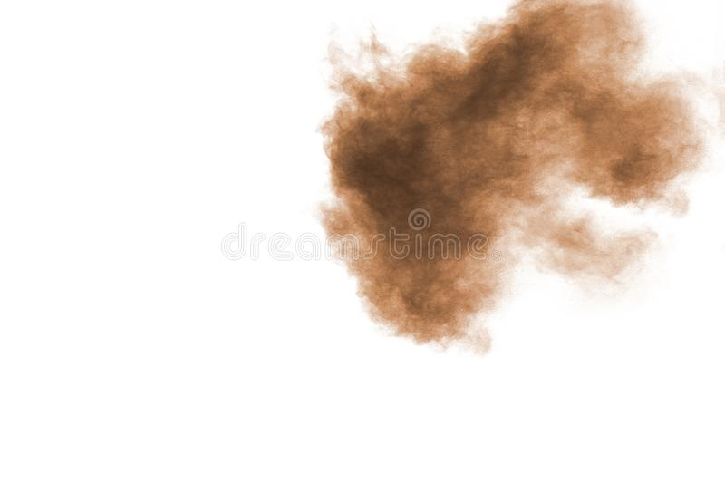 Freeze motion of brown powder exploding. Abstract design of brown dust cloud against white background stock photography