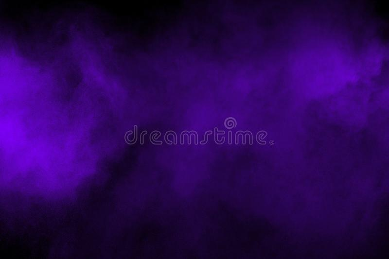 Freeze motion explosion of purple powder dust on a black background. By throwing blue talcum  out of hand. Stopping the movement royalty free stock image