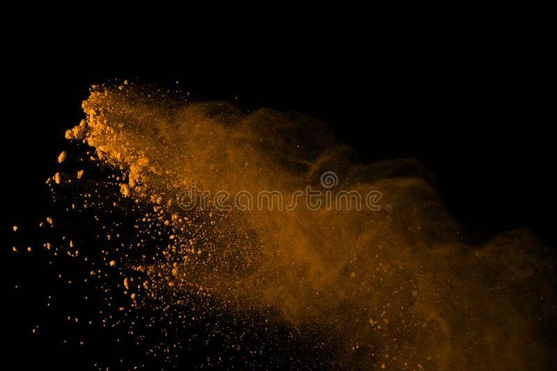 Freeze motion of gold powder explosions isolated on black background. colored dust explosive on dark background. Colorful cloud s. Plashed stock photos