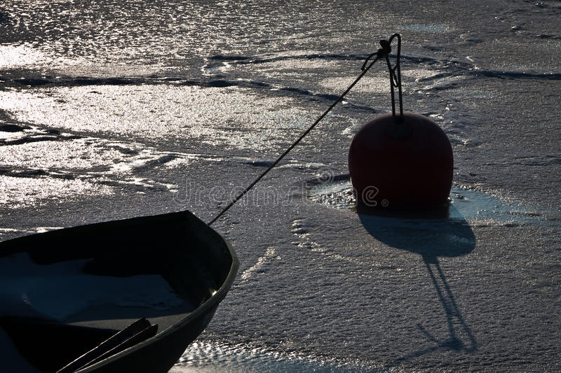 Freezed boat with buoy royalty free stock photography