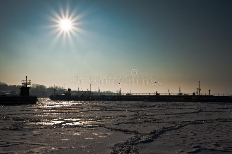 Freezed dock with boats at sunrise royalty free stock images