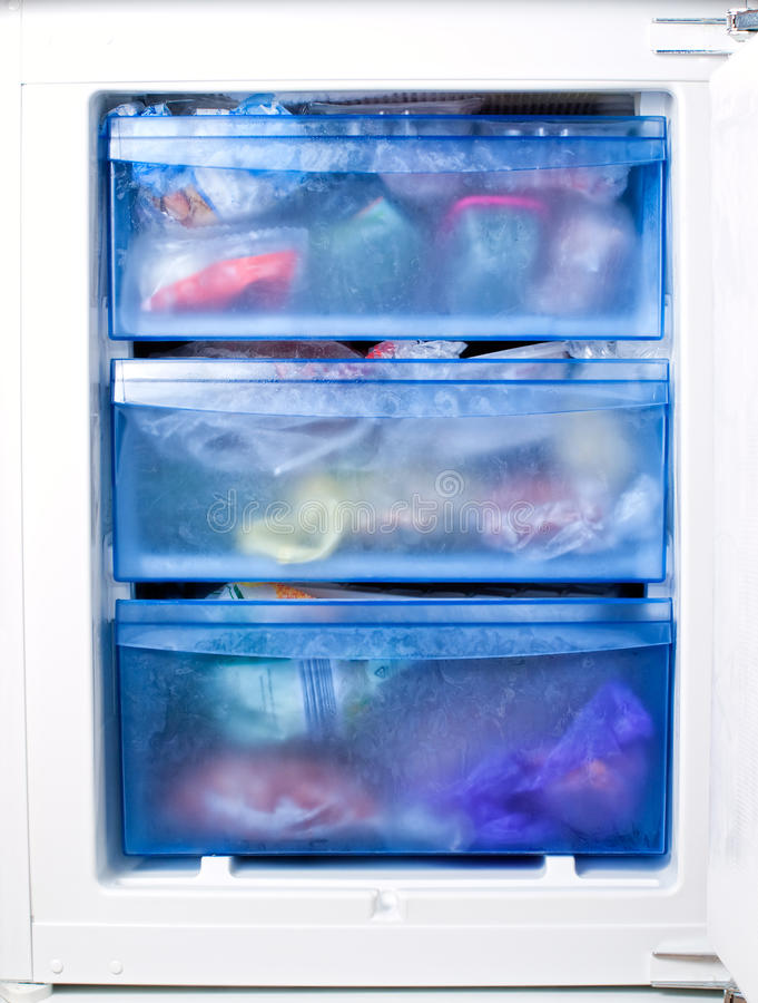 Freezer. View of the inside of a freezer full of various frozen foodstuff stock photos