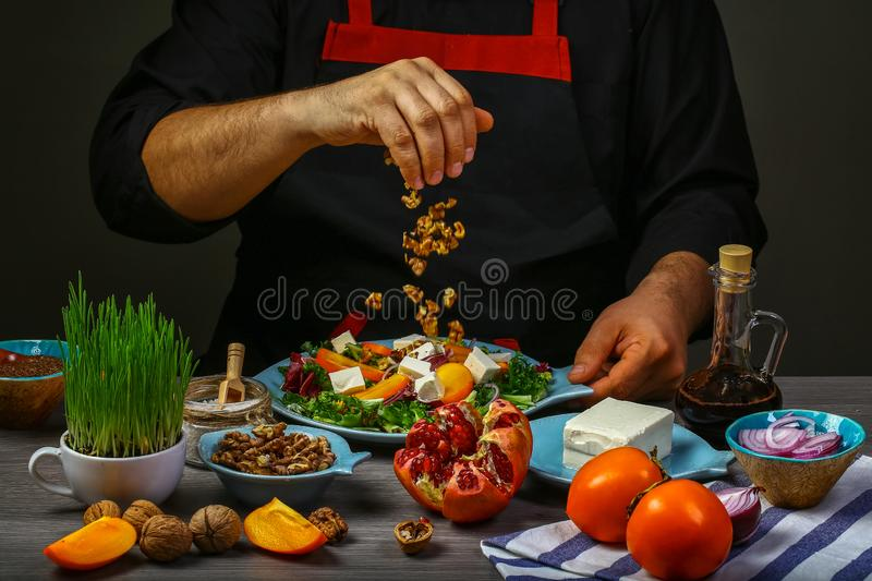 Freezer food prepare in process vegetarian salad with fruits and greens by chef hand in home kitchen. Dark black background. menu. Restaurant stock images