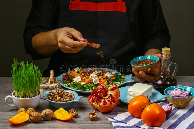 Freezer food prepare in process vegetarian salad with persimmon, arugula, nuts and feta cheese by chef hand in home kitchen. Dark. Black background. menu stock photography