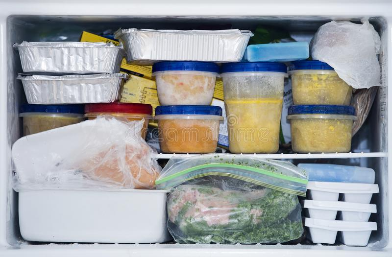 A packed freezer with soup and chicken. A freezer packed with chicken, soup and various frozen food stock photo
