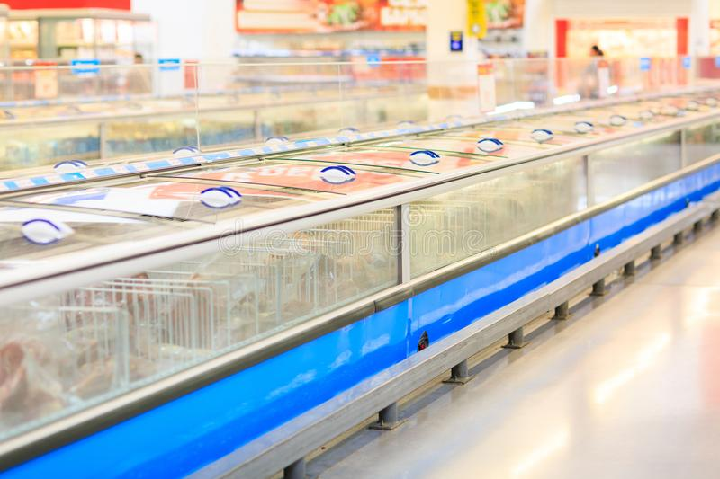 View of freezers in a super market on a blurred background. Freezers for food and frozen seafood are in the supermarket for customers. A lot of boxes for royalty free stock photos