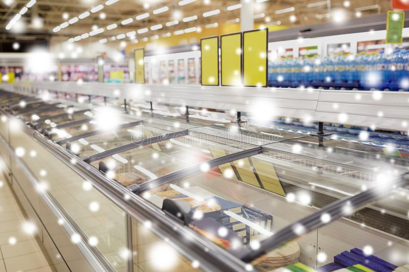 Freezers at grocery store. Sale, shopping, consumerism and storage concept - freezers at grocery store over snow stock photo