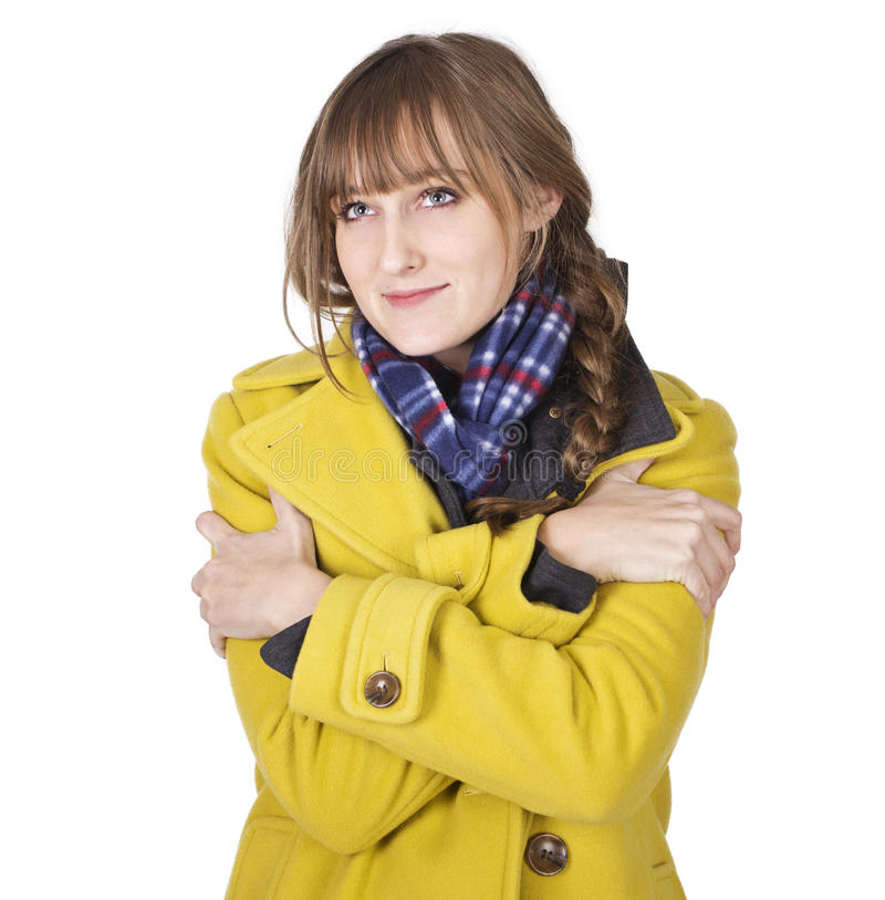 Freezing Cold Young Woman. A shivering, freezing cold woman in her yellow winter coat. Isolated on white royalty free stock photography