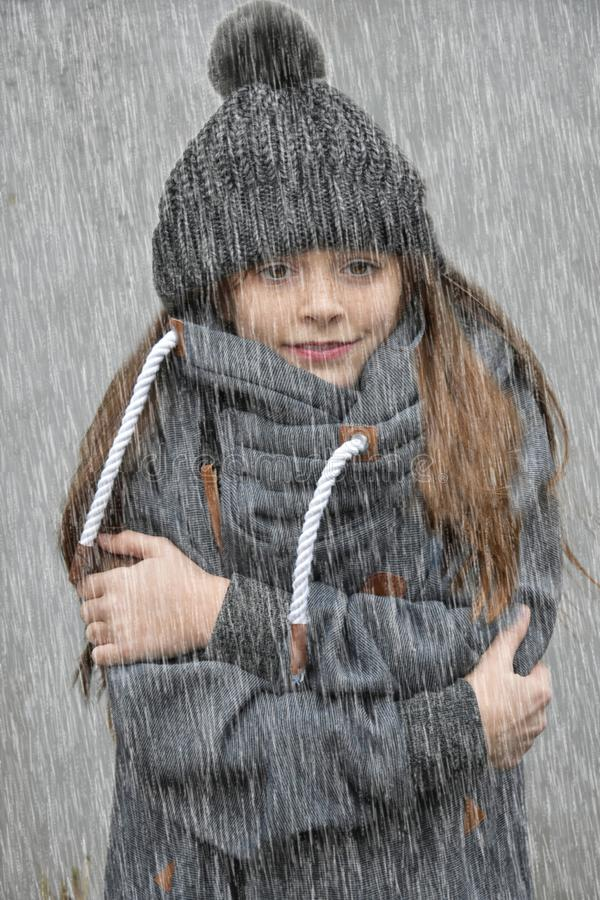 Freezing girl with bobble hat standing in the rain. Freezing girl with bobble hat and woolen sweater standing in the rain royalty free stock photography