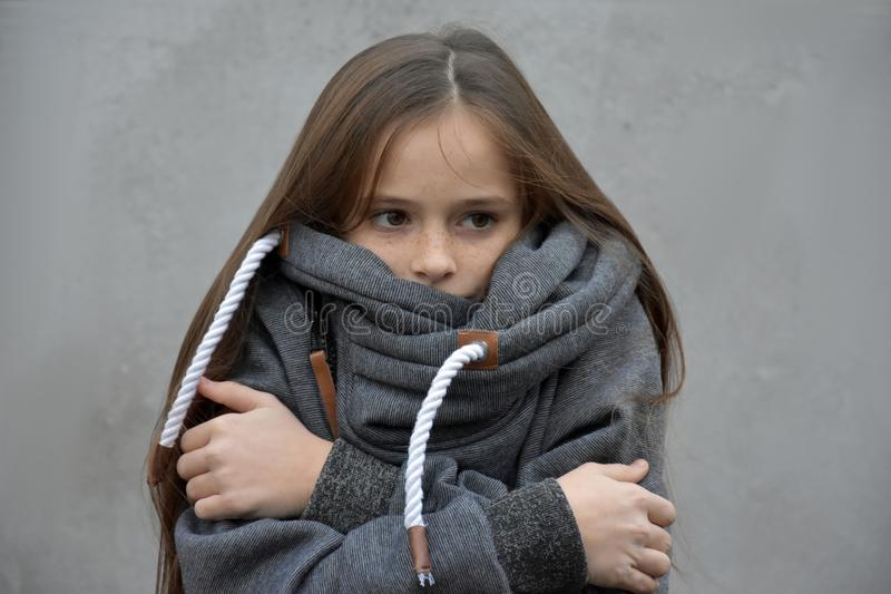 Freezing girl snuggles in her woolen sweater. Freezing girl with wonderful long brown hair snuggles in her new woolen sweater stock photography