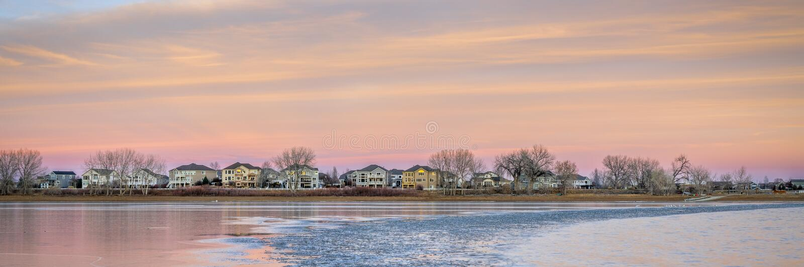 Freezing lake after sunset. With houses at waterfront - Boyd Lake in northern Colorado, panoramic banner stock image
