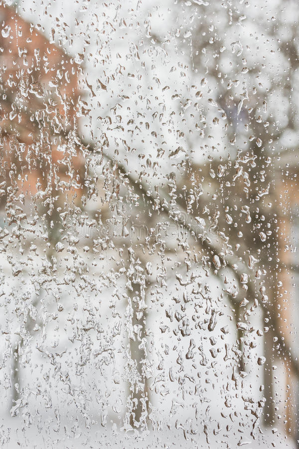 Freezing rain outside the window in inclement winter weather. Texture of the ice and drops on the window glass in inclement winter weather, close up royalty free stock image