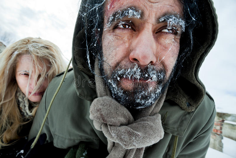 Freezing struggling couple survivers stock photos
