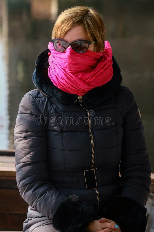 Freezing woman cowers her face with a pink scarf. She is sitting in a boat on the banks of the river royalty free stock images