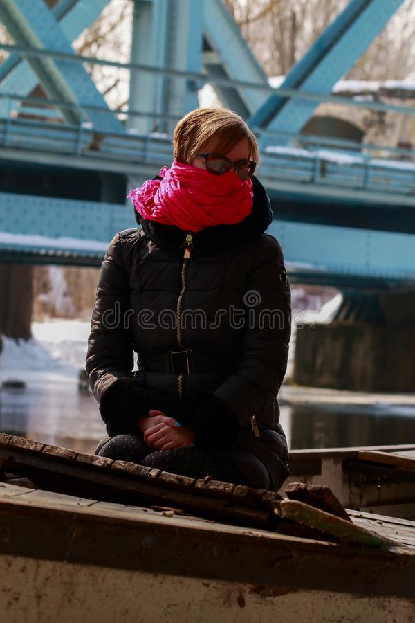 Freezing woman cowers her face with a pink scarf. She is sitting in a boat on the banks of the river.íin the backround the silhouette of a bridge stock photography