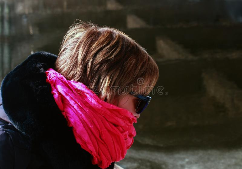 Freezing woman cowers her face with a pink scarf. She is sitting in a boat on the banks of the river stock photography