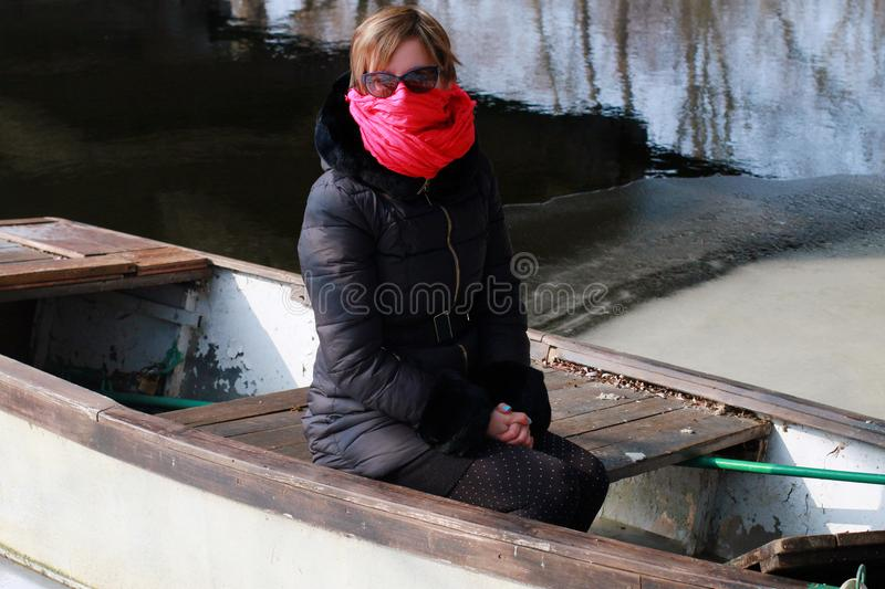 Freezing woman cowers her face with a pink scarf. She is sitting in a boat on the banks of the river stock photo
