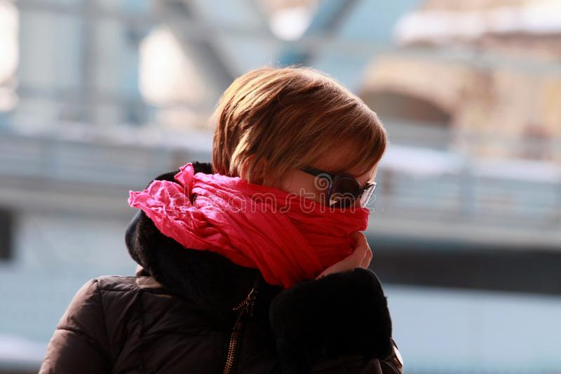 Freezing woman cowers her face with a pink scarf. She is sitting in a boat on the banks of the river.In the backround the silhouette of a bridge stock photos