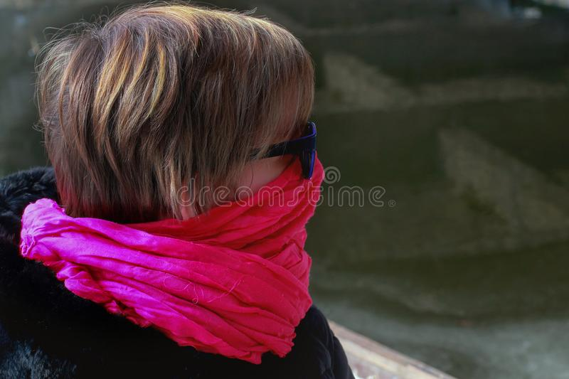 Freezing woman cowers her face with a pink scarf. She is sitting in a boat on the banks of the river.In the backround the silhouette of a bridge stock image