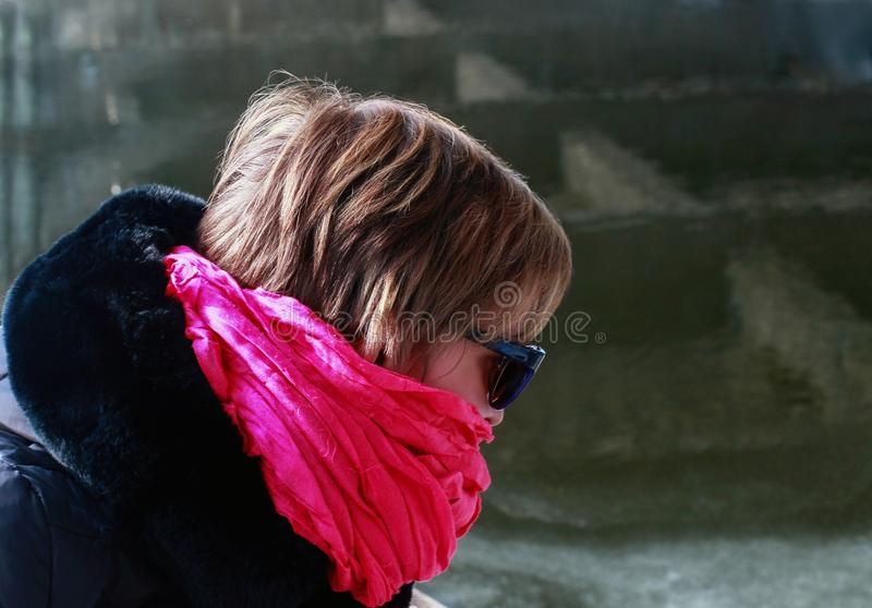 Freezing woman cowers her face with a pink scarf. She is sitting in a boat on the banks of the river royalty free stock image