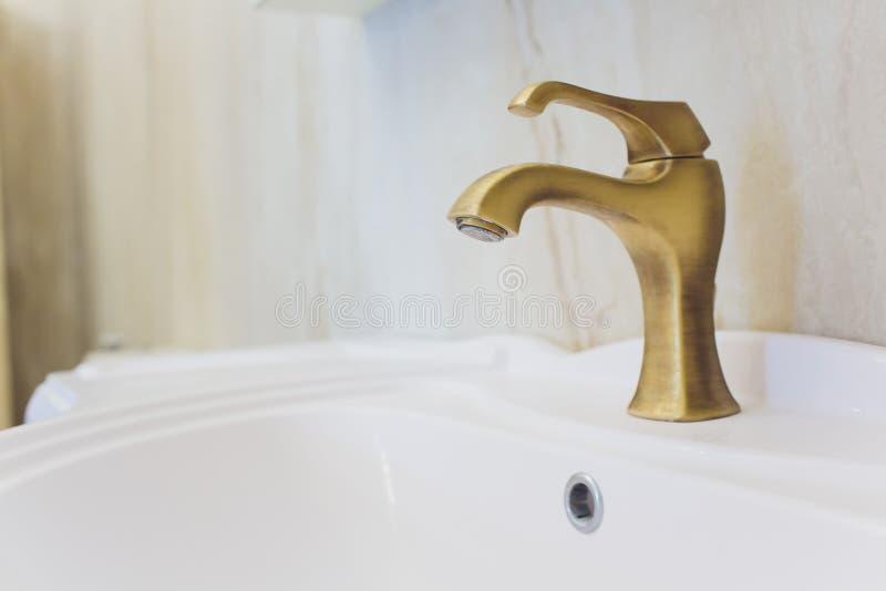 Fregadero cercano interior de la opinión del cuarto de baño blanco, grúa, válvulas y espejo plateado tallado adornado rico del or imagenes de archivo