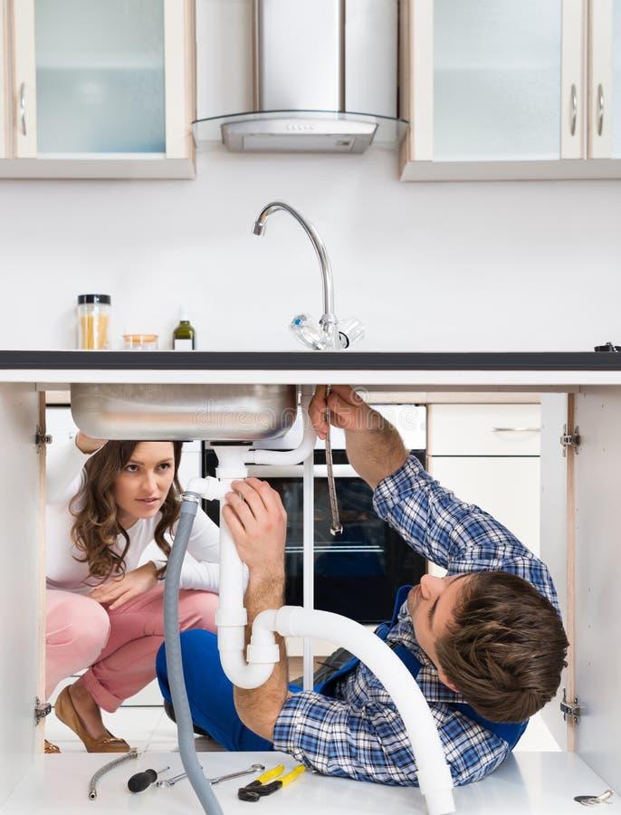 Fregadero de la fijación del trabajador en Front Of Woman In Kitchen fotografía de archivo libre de regalías